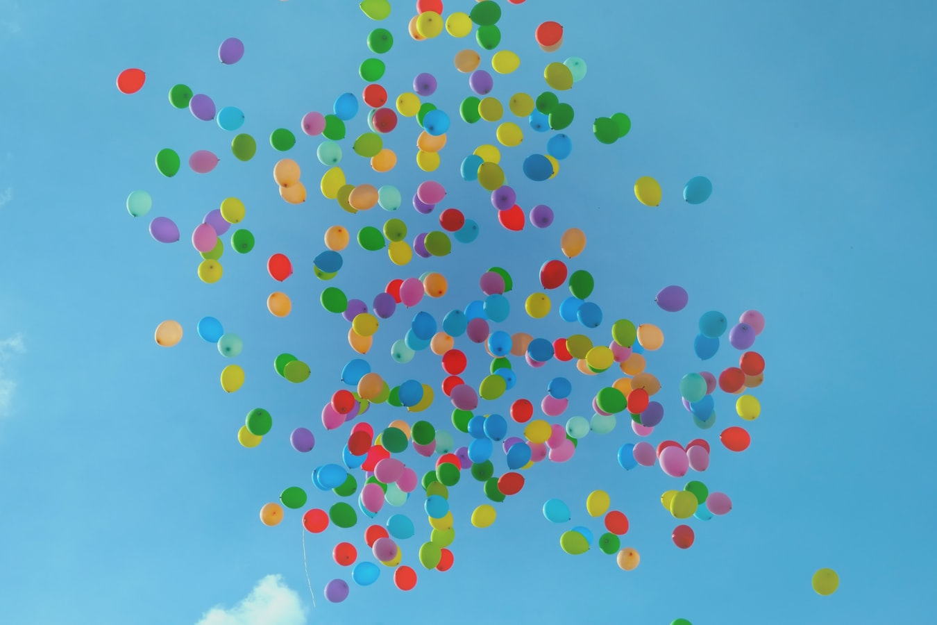 A group of many colourful balloons float in the sky.