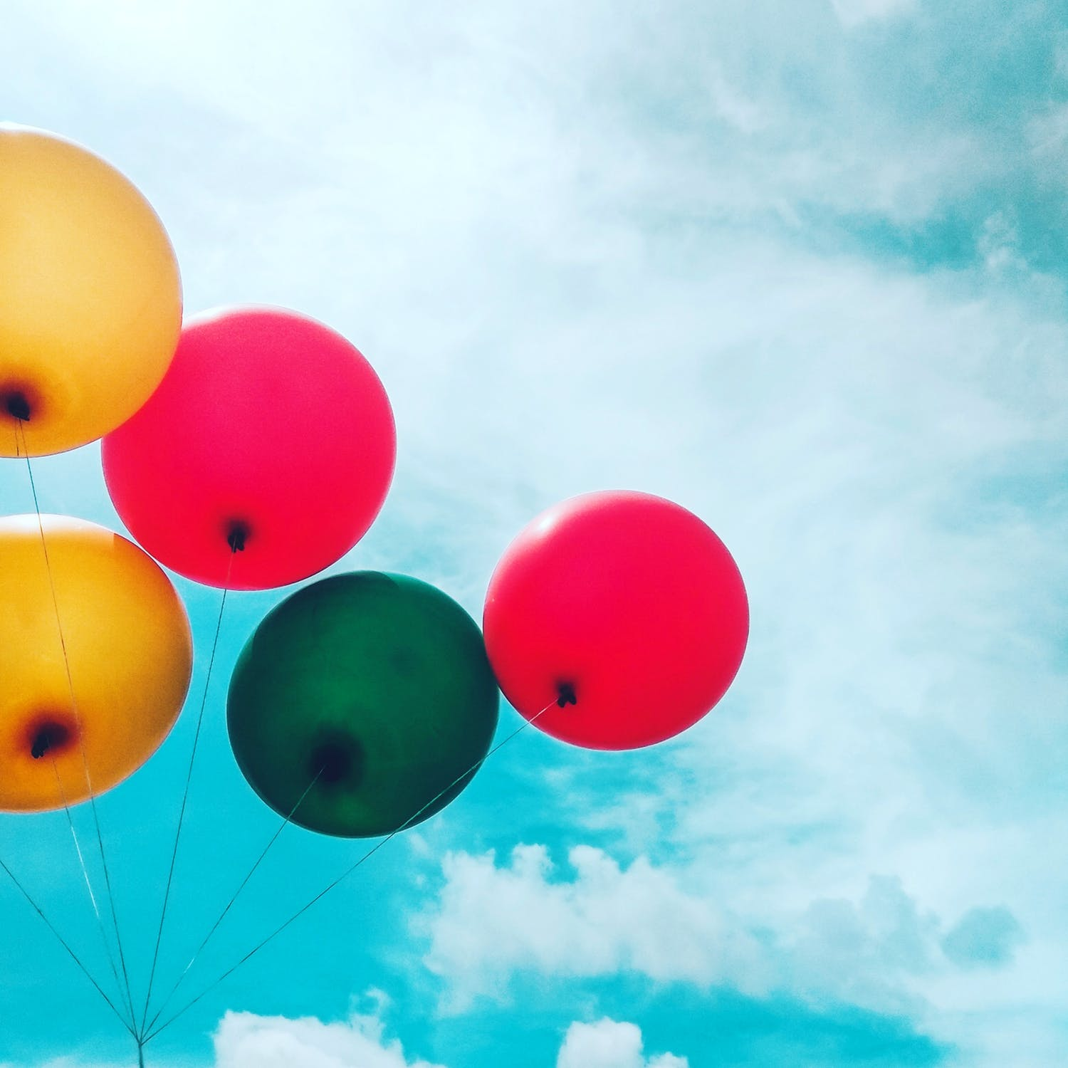 Yellow, green and red balloons below the blue sky.