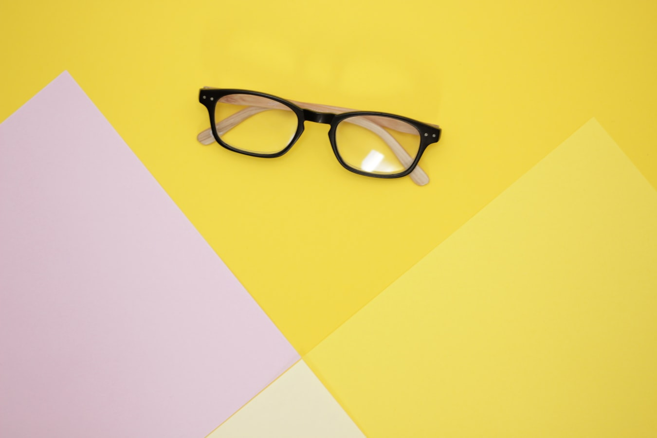 A pair of glasses on a yellow background.