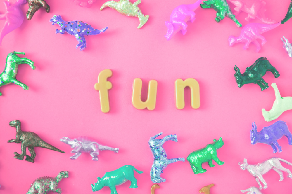 Letters spell out 'fun' and is surrounded by toy dinosaurs.
