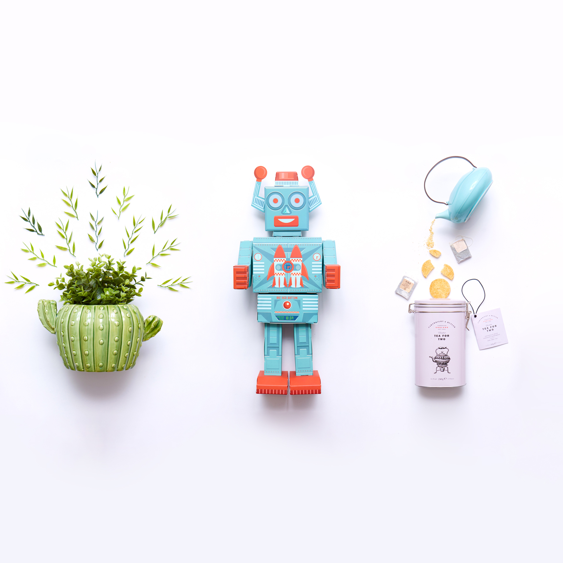 Top down shot of a cactus plant pot, a blue and red robot toy and a tin of biscuits.