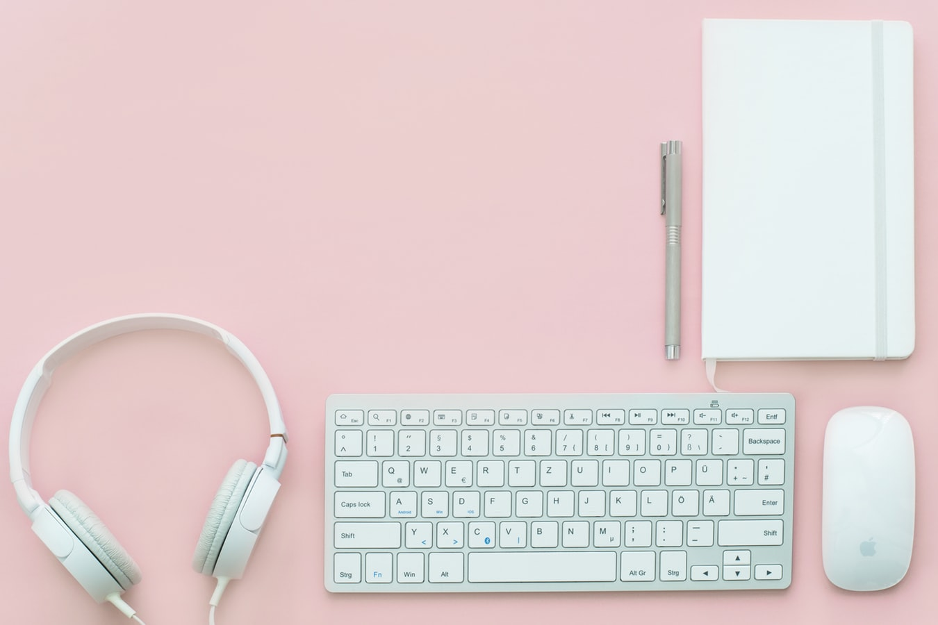 A pair of headphones, keyboard, pen, mouse and a journal on a pink background